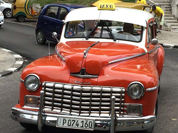 Red and white vintage taxi in Havana.