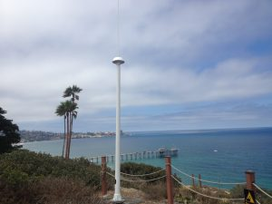 Codar antenna set up on shoreline with palm trees behind