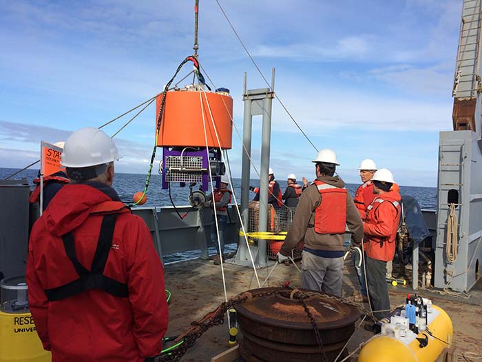 crew stand on deck while working to deploy the environmental sample processor into the Pacific