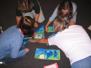 Children working on an ocean observing puzzle on the floor