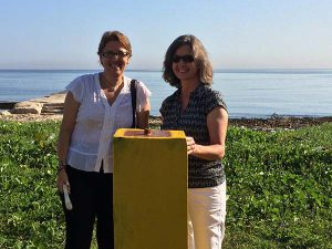 Two women stand by Geodetic marker in Cuba.
