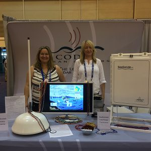 Two women stand at an exhibit booth with codar products