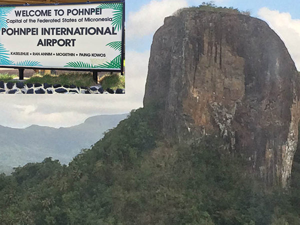 Aerial of a mountain taken from a plane approaching Pohnpei, Micronesia.  Inset of Pohnpei International Airport sign.