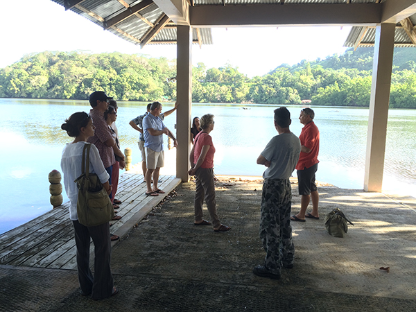 Group standing under an outdoor shelter by a lagoon