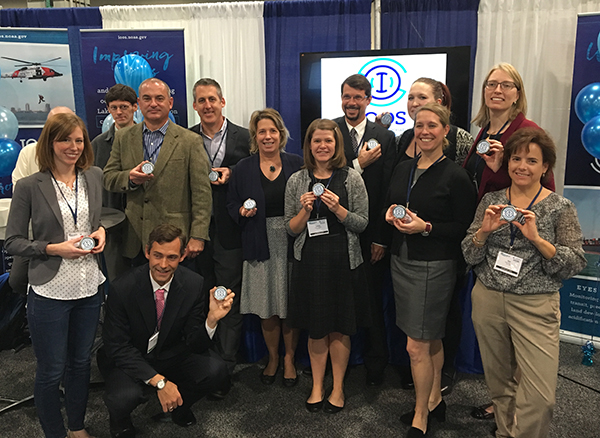 All IOOS program staff standing together and holding commemorative tins featuring the IOOS logo at Oceans '15.