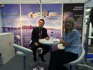 man and woman seated at a table in their booth at Oceanology International