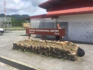 Zdenka Willis standing behind The Kosrae Airport sign, Kosrae, Federated States of Micronesia