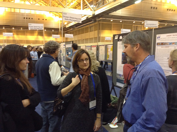 three people having a discussion in the exhibit hall at AGU Ocean Sciences