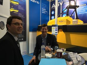 two men sit in an exhibit booth at Oceanology International next to a display underwater vehicle.