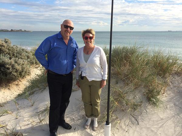 Tim Moltmann and Zdenka Willis stand on a beach with an HF Radar installation